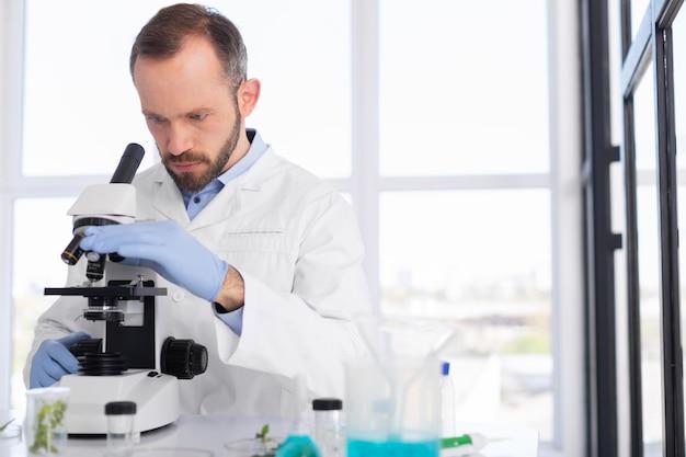 Wetenschappers die het middelgroot schot van de laboratoriumjas dragen
