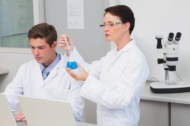 Wetenschappers die met laptop werken en een beker gebruiken
