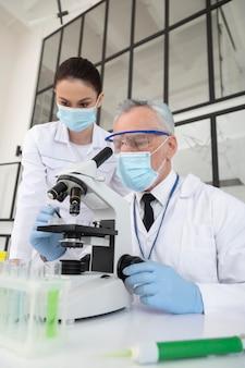 Wetenschappers die met microscoop in laboratorium werken