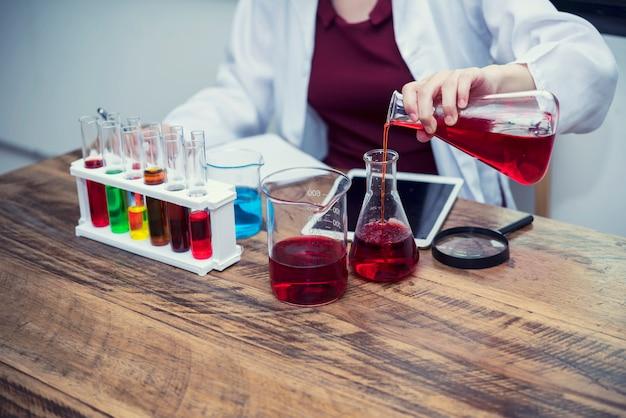 Wetenschappers die oplossingsresultaat aan het tabletscherm kijken op laboratoriumlijst met laboratoriumtoebehoren.