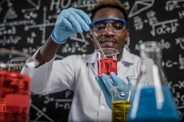 Wetenschappers die rode chemische producten in glas mengen bij het laboratorium.