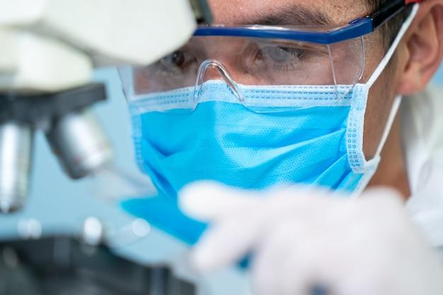Wetenschappers die werken in het laboratorium, close-up van artsen in beschermende kleding van hazmat ppe dragen medische rubberen handschoenen gebruik microscoop in het laboratorium.