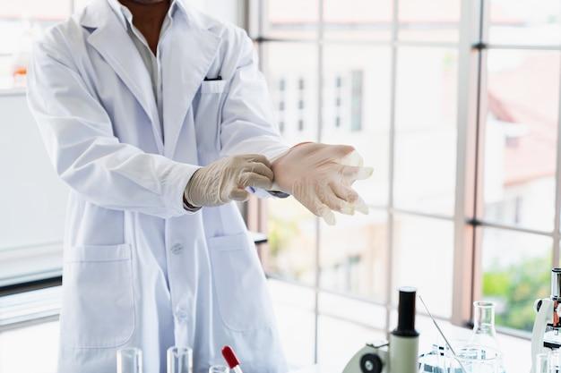 Wetenschappers dragen handschoenen tijdens onderzoek in wetenschapslaboratoria