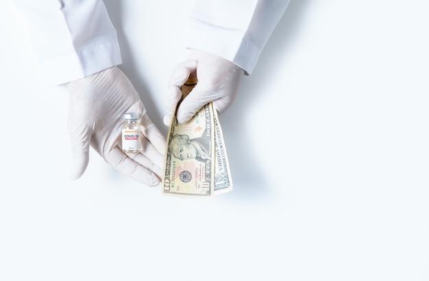 Wetenschappers dragen rubberen handschoenen met covid-19-vaccinflessen en amerikaanse dollars die op een witte achtergrond worden geïsoleerd