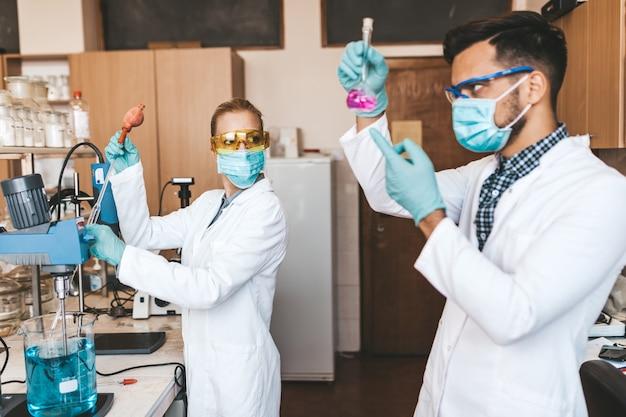 Wetenschappers en onderzoekers van middelbare leeftijd met gezichtsbeschermende maskers werken in een chemisch laboratorium aan het coronavirusvaccin.