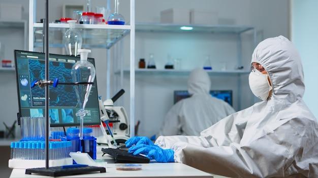 Wetenschappers in beschermingspakken die in chemisch uitgerust laboratorium werken. team van biologen die de evolutie van vaccins onderzoeken met behulp van hightech en technologie die de behandeling tegen het covid19-virus onderzoeken
