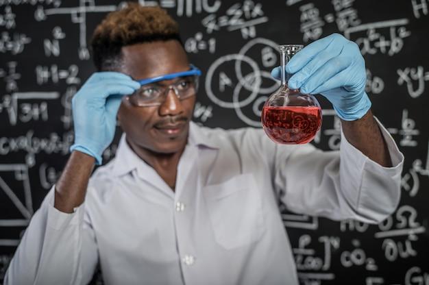 Wetenschappers kijken naar de rode chemische stof in het glas in het laboratorium en hanteren de bril met de hand