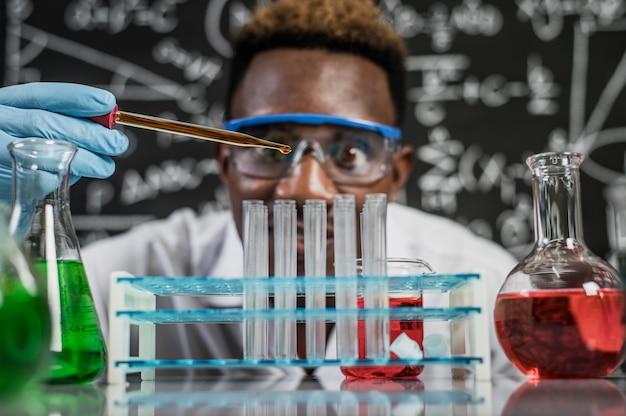 Wetenschappers laten in het laboratorium oranje chemicaliën in het glas vallen