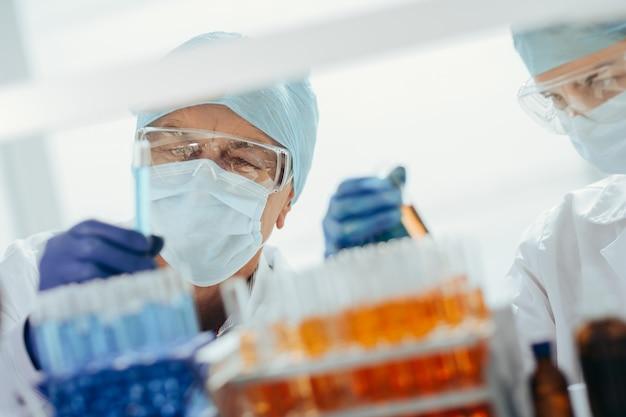 Wetenschappers met beschermende maskers staan voor een rek met reageerbuisjes