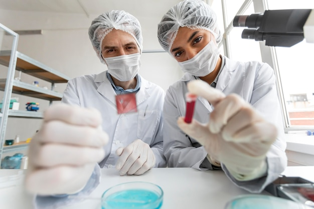 Wetenschappers met buis en glasplaatje sluiten omhoog
