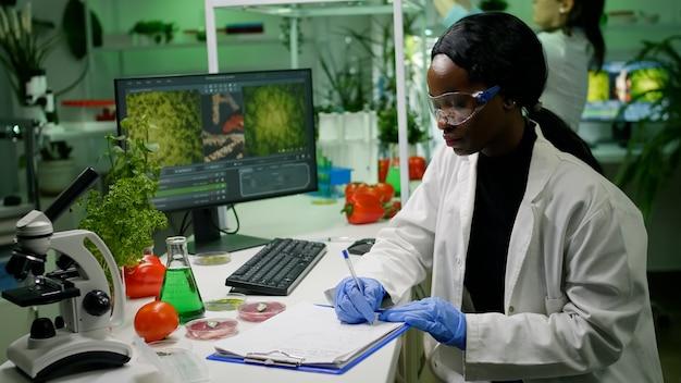 Wetenschappers-onderzoekers die in een biotechnologisch laboratorium werken, kijken naar veganistisch voedsel en jonge boompjes die genetische mutaties analyseren en biologische expertise schrijven op notitieblok. farmaceutisch onderzoek biochemie