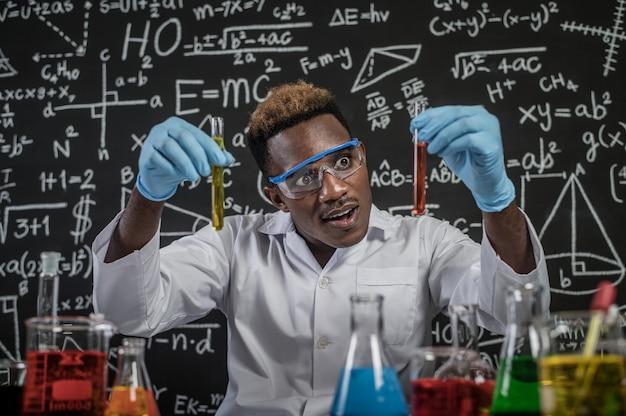 Wetenschappers schrokken van de oranje chemische stof in het glas in het laboratorium