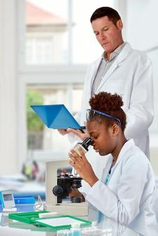 Wetenschappers, senior blanke mannen en jonge afrikaanse vrouwen, werken in onderzoeksfaciliteit