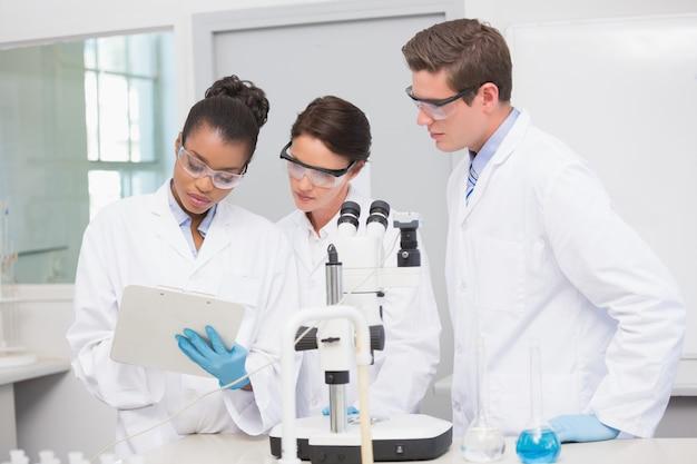 Wetenschappers werken met een microscoop en maken aantekeningen