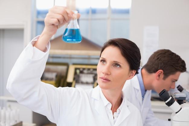 Wetenschappers werken met microscoop en bekerglas