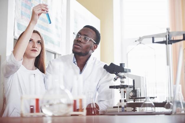 Wetenschappers werken nauw samen met de microscoop in het laboratorium door experimenten en analyses uit te voeren.