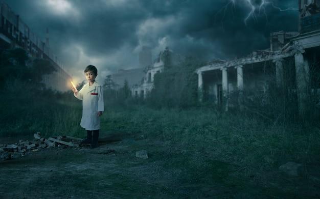 Wetenschappersjongen die een spuit vasthoudt met de remedie voor de pandemie in een apocalyptisch scenario met verwoeste gebouwen