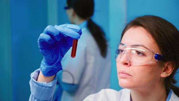 Wetenschappervrouw die bloedmonsters en vloeistof onderzoekt die in een modern uitgerust laboratorium werken