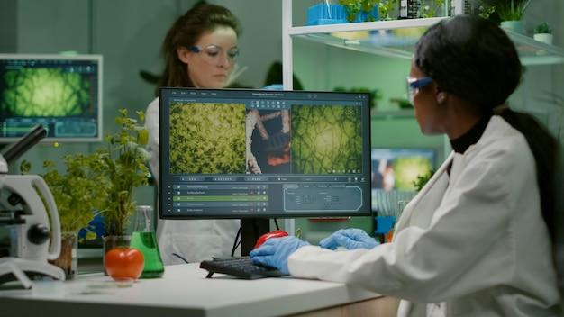 Wetenschappervrouw die microbiologische expertise typt op de computer