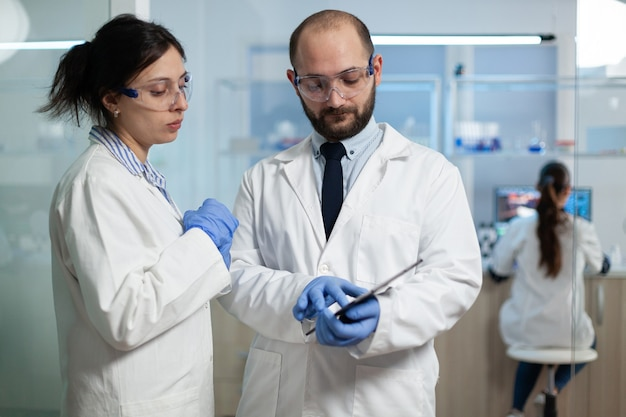 Wetenschappervrouw die virusexpertise analyseert met bioloogonderzoeker