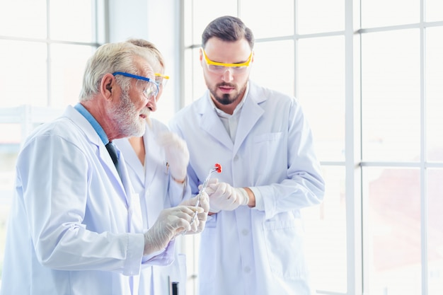 Wetenschapsleraar en studententeam die met chemische producten in laboratorium werken