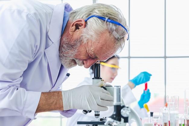 Wetenschapsmensen die met microscopenchemische producten werken in laboratorium