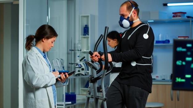 Wetenschapssportarts die patiënt vraagt naar zijn gezondheid terwijl sportman op crosstrainer loopt met masker en elektroden op het lichaam bevestigd