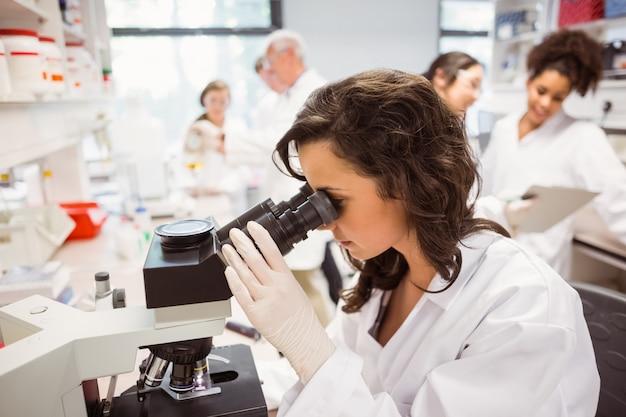 Wetenschapsstudent die door microscoop in het laboratorium aan de universiteit kijkt