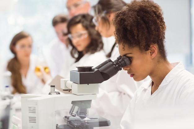 Wetenschapsstudent die door microscoop in het laboratorium kijkt