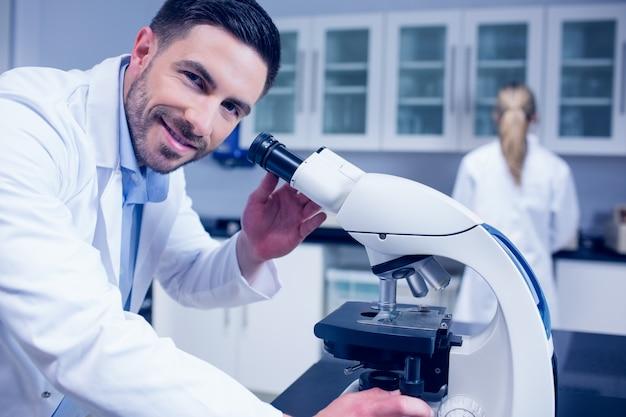 Wetenschapsstudent die met microscoop in het laboratorium werkt