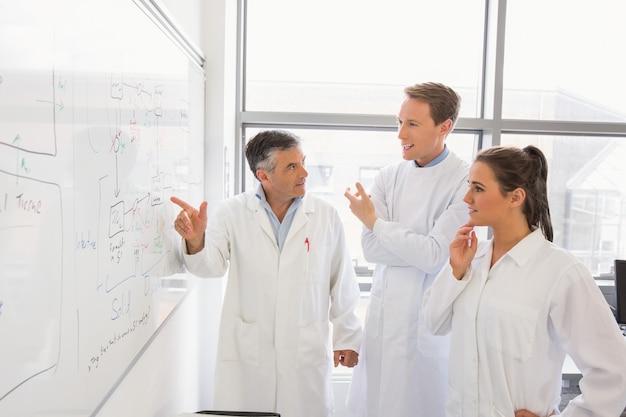 Wetenschapsstudenten en spreker die whiteboard bekijken