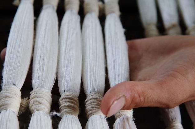 Weven en vervaardigen van garen close-up. de hand houdt kant-en-klaar garen vast