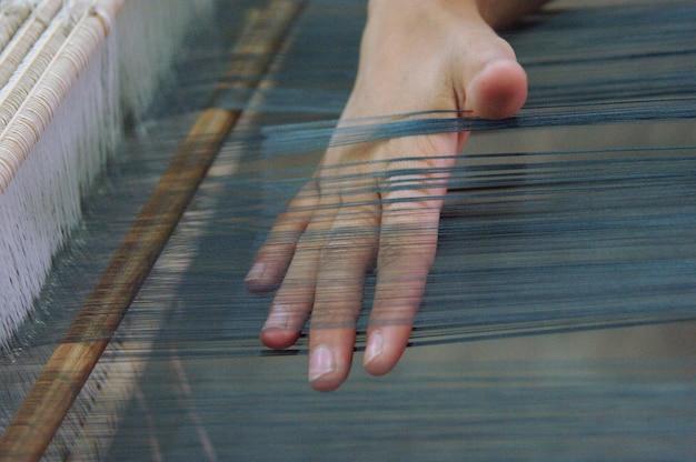 Weven en vervaardigen van handgemaakte stof close-up. vrouwenhanden achter een weefgetouw maken doek