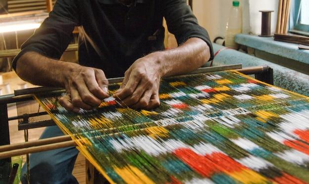 Weven en vervaardigen van handgemaakte tapijten close-up. mensenhanden achter een weefgetouw