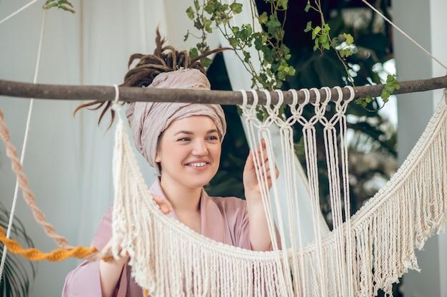 Weven. jonge vrouw in een hoofddeksel die tevreden kijkt tijdens het weven van macramé