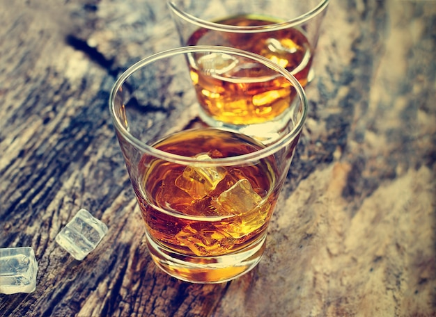 Whiskeybourbon met ijs op houten textuurachtergrond.