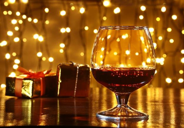Whisky, cognac, cognac en geschenkdoos op houten tafel. vieringssamenstelling op het licht