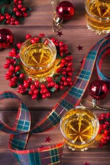 Whisky, cognac of sterke drank geschoten en kerstversiering op houten achtergrond. seizoensgebonden vakantie concept. overhead