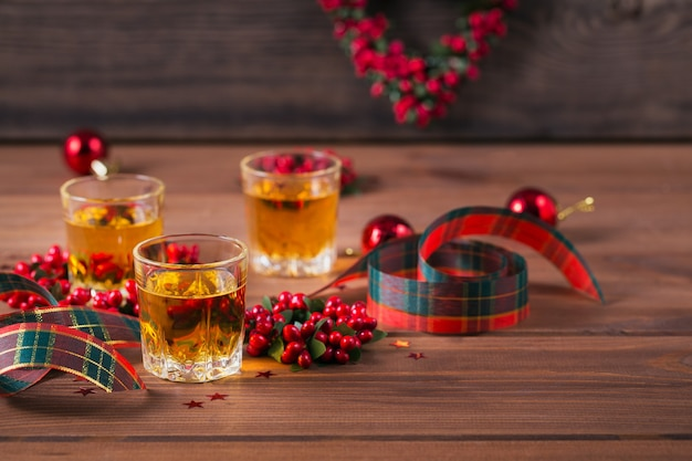 Whisky, cognac of sterke drank geschoten en kerstversiering op houten achtergrond. seizoensgebonden vakantie concept.