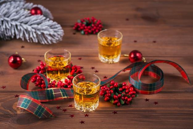 Whisky, cognac of sterke drank geschoten en kerstversiering op houten achtergrond. wintervakantie concept.