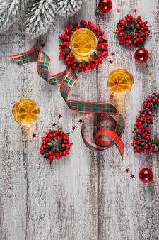 Whisky, cognac of sterke drank geschoten en kerstversiering op witte houten achtergrond. seizoensgebonden vakantie concept. plat leggen