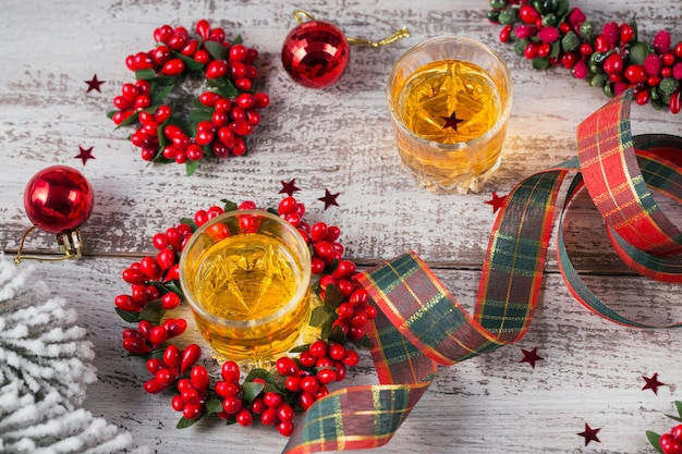 Whisky, cognac of sterke drank geschoten en kerstversiering op witte houten achtergrond. seizoensgebonden vakantie concept.