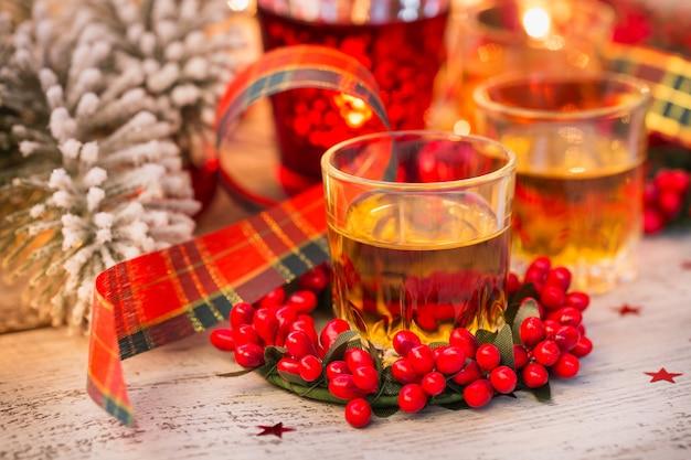 Whisky, cognac of sterke drank geschoten en kerstversiering op witte houten achtergrond. wintervakantie concept. detailopname