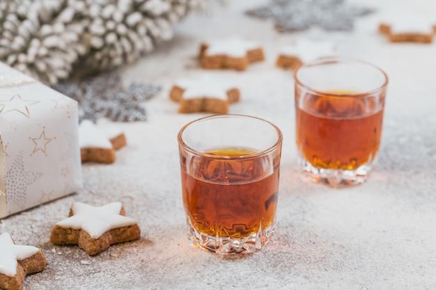 Whisky, cognac of sterke drank, koekjes en kerstversieringen op wit