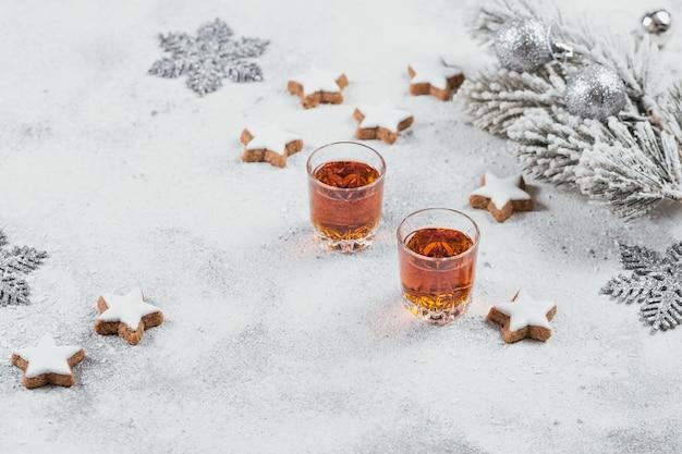 Whisky, cognac of sterke drank, koekjes en kerstversieringen op witte achtergrond. wintervakantie concept.