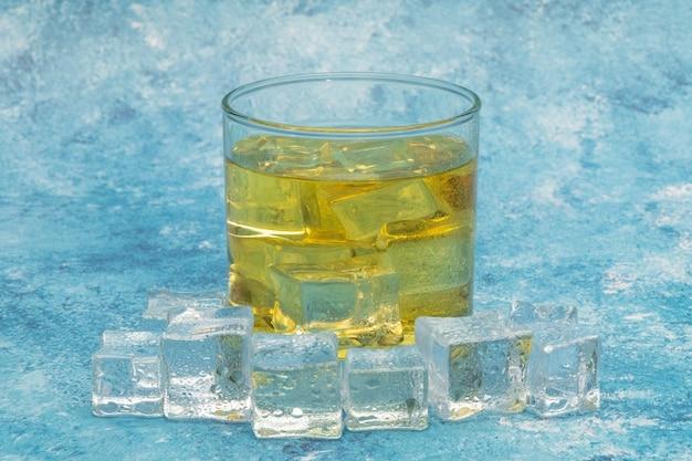Whisky in de rotsen, glas whisky met ijsblokjes