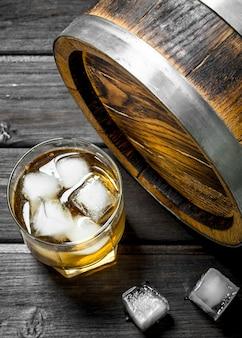 Whisky in een glas met ijsblokjes en een vat.
