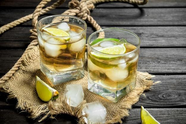Whisky in een glas met limoen en ijs op de zak. op zwart houten