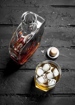 Whisky in een glazen fles en een glas ijs. op zwarte rustiek