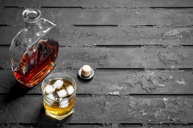 Whisky in een glazen fles en een glas ijs.